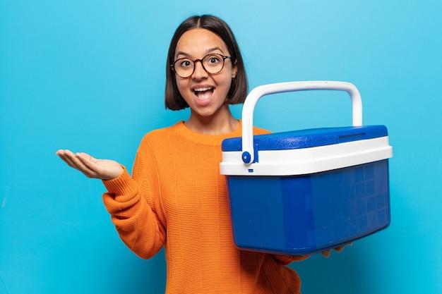 Jovem mulher latina se sentindo feliz, animada, surpresa ou chocada, sorrindo e atônita com algo inacreditável