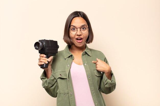 Jovem mulher latina se sentindo feliz, surpresa e orgulhosa, apontando para si mesma com um olhar animado e surpreso