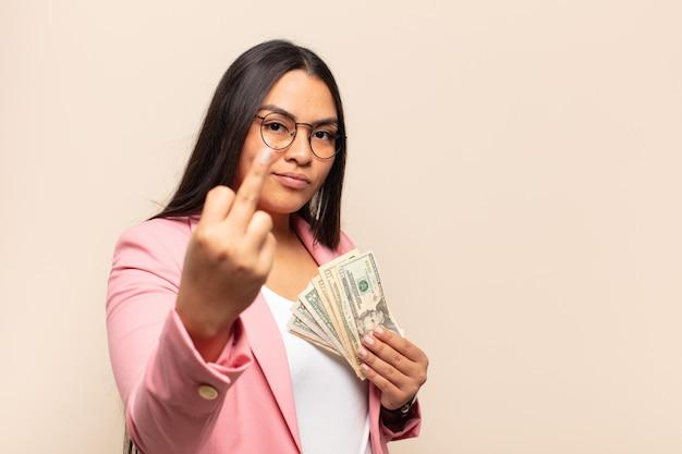 Jovem mulher latina se sentindo irritada, irritada, rebelde e agressiva, sacudindo o dedo do meio e revidando