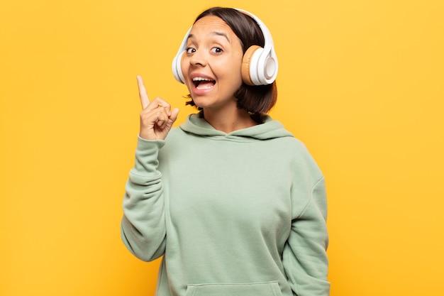 Jovem mulher latina se sentindo um gênio feliz e animado depois de realizar uma ideia, levantando o dedo alegremente, eureka!