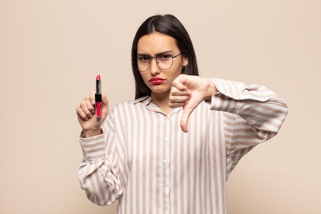 Jovem mulher latina se sentindo zangada, irritada, decepcionada ou descontente, mostrando o polegar para baixo com um olhar sério