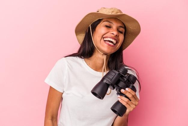 Jovem mulher latina segurando binóculos isolados no fundo rosa ri alto, mantendo a mão no peito.