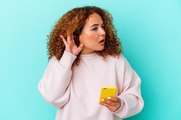 Jovem mulher latina segurando celular isolado em fundo azul, tentando ouvir uma fofoca.