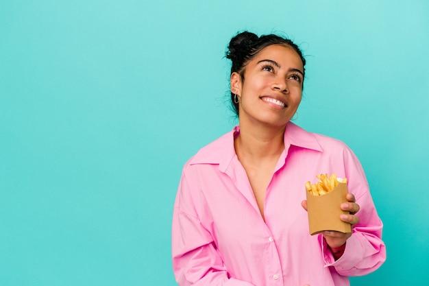 Jovem mulher latina segurando fichas isoladas em um fundo azul, sonhando em alcançar objetivos e propósitos