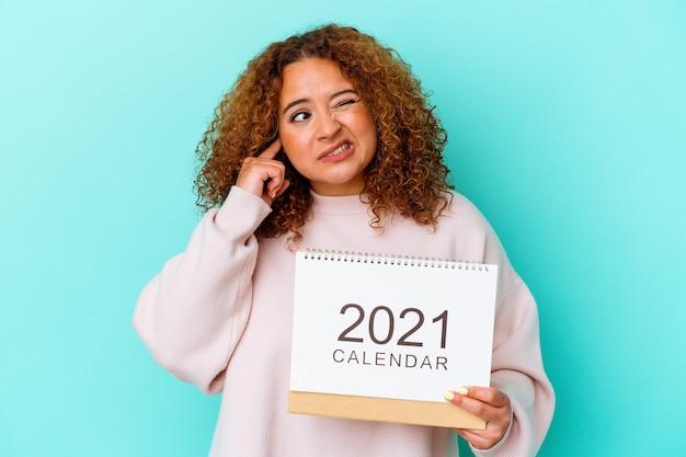 Jovem mulher latina segurando um calendário isolado na parede azul, cobrindo as orelhas com as mãos