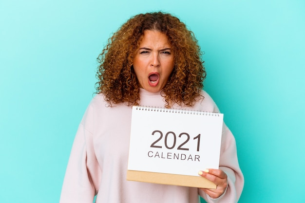 Jovem mulher latina segurando um calendário isolado na parede azul, gritando muito zangada e agressiva