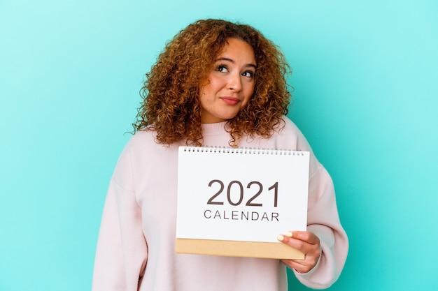 Jovem mulher latina segurando um calendário isolado na parede azul, sonhando em alcançar objetivos e propósitos