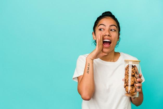 Jovem mulher latina segurando um pote de biscoitos isolado em um fundo azul está contando uma notícia secreta de travagem e olhando para o lado