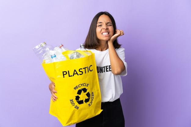 Jovem mulher latina segurando um saco de reciclagem cheio de papel para reciclar isolado em roxo frustrado e orelhas em forma de cone