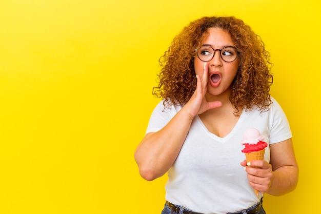 Jovem mulher latina segurando um sorvete isolado em um fundo amarelo está contando uma notícia secreta de travagem e olhando para o lado