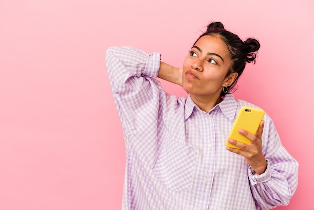 Jovem mulher latina segurando um telefone celular isolado no fundo rosa, tocando a parte de trás da cabeça, pensando e fazendo uma escolha.