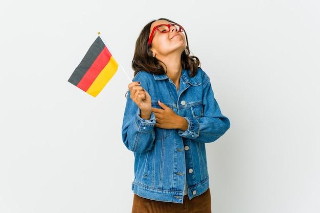 Jovem mulher latina segurando uma bandeira alemã abraços, sorrindo despreocupada e feliz.