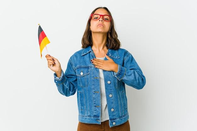 Jovem mulher latina segurando uma bandeira alemã, fazendo um juramento, colocando a mão no peito.