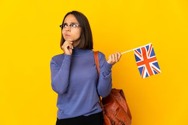 Jovem mulher latina segurando uma bandeira do reino unido, isolada em um fundo amarelo, tendo dúvidas e pensando