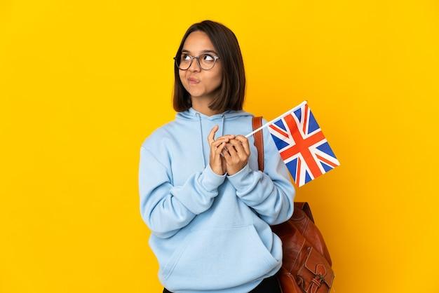Jovem mulher latina segurando uma bandeira do reino unido, isolada em um fundo amarelo, tramando algo