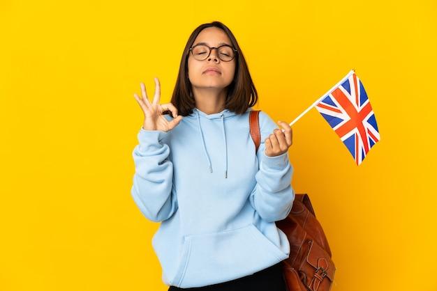Jovem mulher latina segurando uma bandeira do reino unido isolada na parede amarela em pose zen