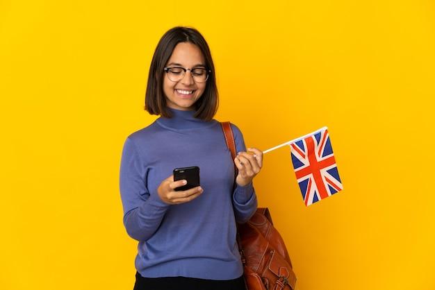 Jovem mulher latina segurando uma bandeira do reino unido isolada na parede amarela enviando uma mensagem com o celular