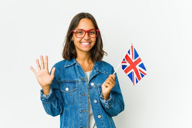 Jovem mulher latina segurando uma bandeira inglesa isolada na parede branca, mostrando o número dez com as mãos.