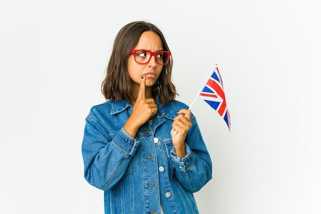 Jovem mulher latina segurando uma bandeira inglesa isolada na parede branca, olhando de soslaio com expressão duvidosa e cética.