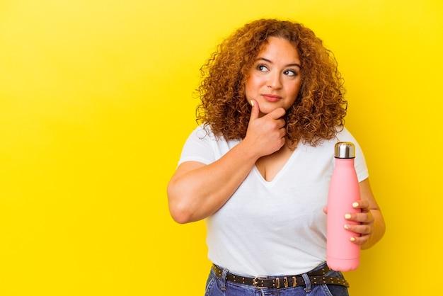 Jovem mulher latina segurando uma garrafa térmica isolada em fundo amarelo, olhando de soslaio com expressão duvidosa e cética.