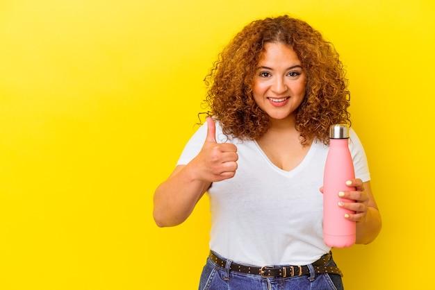 Jovem mulher latina segurando uma garrafa térmica isolada em um fundo amarelo, sorrindo e levantando o polegar