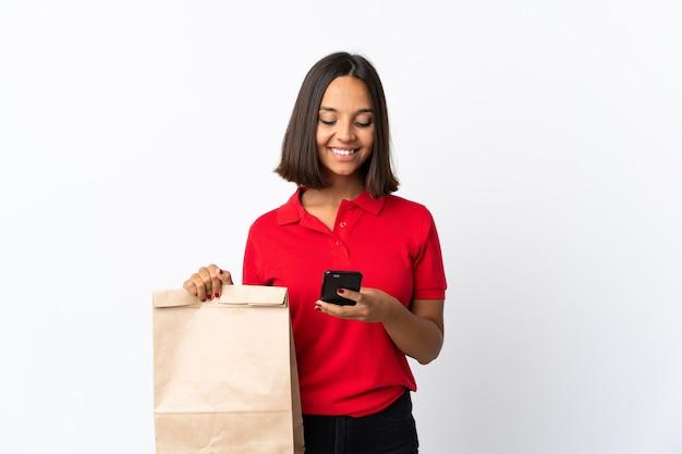 Jovem mulher latina segurando uma sacola de compras de supermercado isolada no branco enviando uma mensagem com o celular