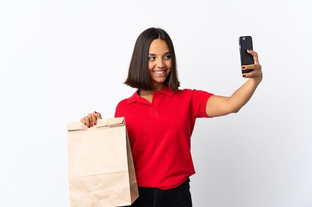 Jovem mulher latina segurando uma sacola de compras de supermercado isolada no branco fazendo uma selfie