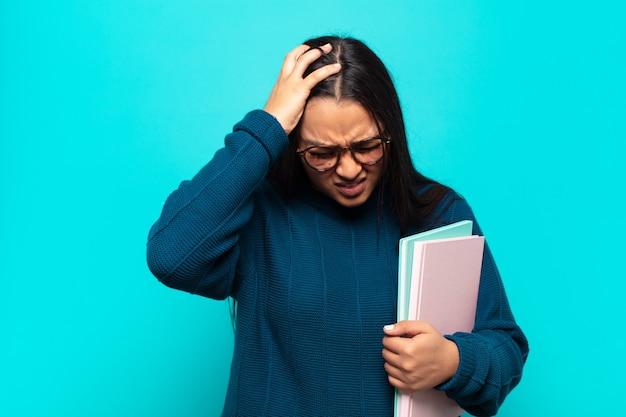 Jovem mulher latina sentindo-se estressada e frustrada, levando as mãos à cabeça, sentindo-se cansada, infeliz e com enxaqueca