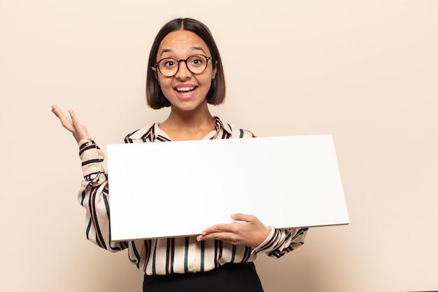 Jovem mulher latina sentindo-se feliz, surpresa e alegre, sorrindo com atitude positiva, percebendo uma solução ou ideia