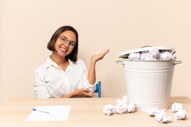Jovem mulher latina sorrindo com orgulho e confiança, sentindo-se feliz e satisfeita e mostrando um conceito no espaço da cópia