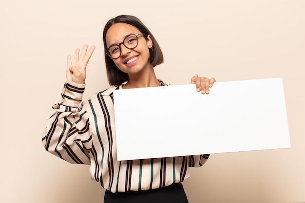 Jovem mulher latina sorrindo e parecendo amigável, mostrando o número quatro ou o quarto com a mão para a frente, em contagem regressiva