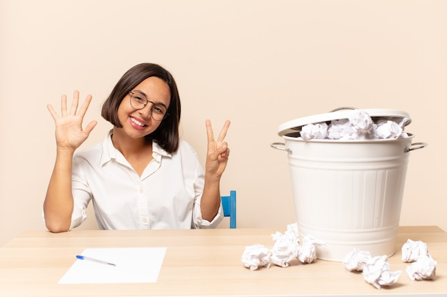 Jovem mulher latina sorrindo e parecendo amigável, mostrando o número sete ou sétimo com a mão para a frente, em contagem regressiva