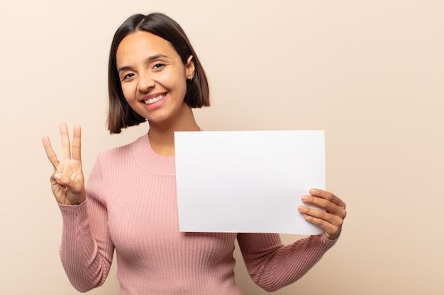 Jovem mulher latina sorrindo e parecendo amigável, mostrando o número três ou o terceiro com a mão para a frente, em contagem regressiva