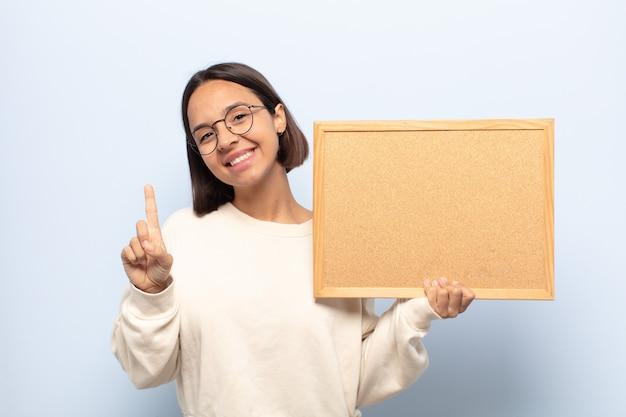 Jovem mulher latina sorrindo e parecendo amigável, mostrando o número um ou primeiro com a mão para a frente, em contagem regressiva