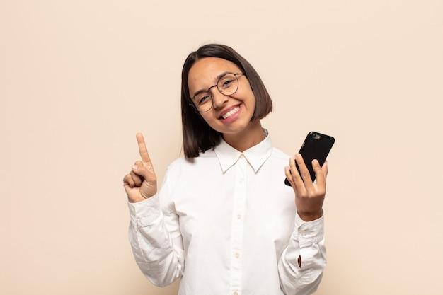 Jovem mulher latina sorrindo e parecendo amigável, mostrando o número um ou primeiro com a mão para a frente, em contagem regressiva Foto Premium