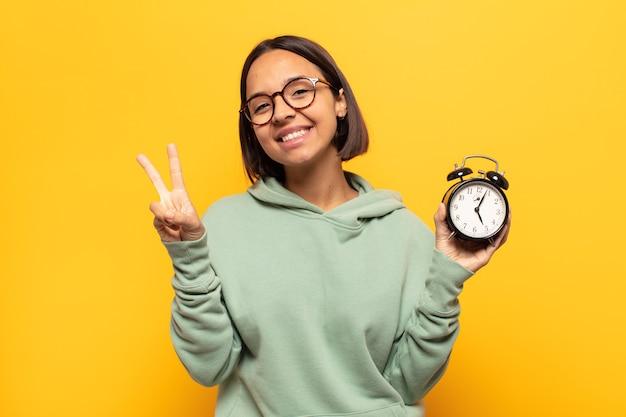 Jovem mulher latina sorrindo e parecendo feliz, despreocupada e positiva, gesticulando vitória ou paz com uma mão