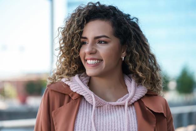 Jovem mulher latina sorrindo em pé ao ar livre na rua. conceito urbano.