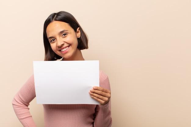 Jovem mulher latina sorrindo feliz com uma mão no quadril e com atitude confiante, positiva, orgulhosa e amigável