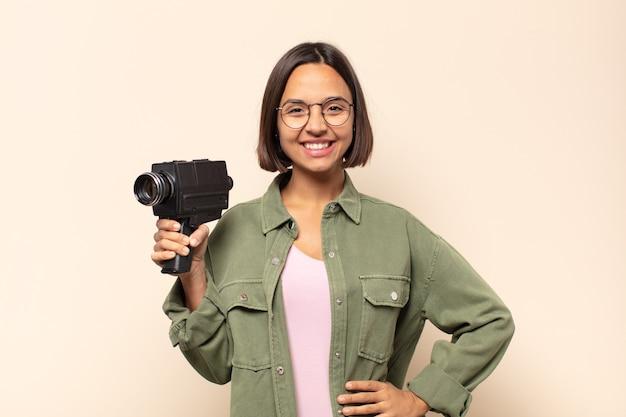 Jovem mulher latina sorrindo feliz com uma mão no quadril e uma atitude confiante, positiva, orgulhosa e amigável