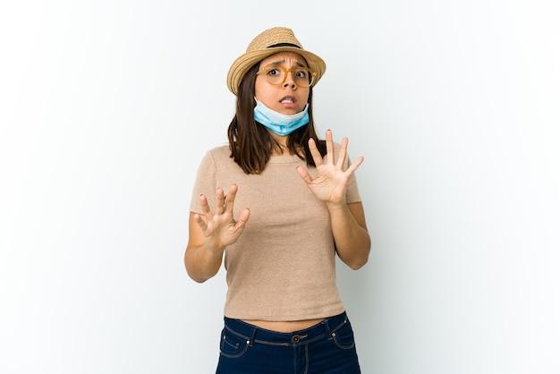 Jovem mulher latina usando chapéu e máscara para se proteger de cobiça isolada na parede branca sendo chocada devido a um perigo iminente