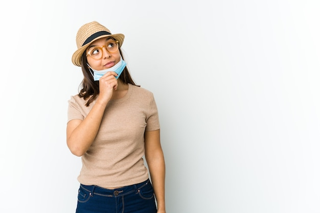 Jovem mulher latina usando chapéu e máscara para se proteger de cobiçoso, isolado na parede branca, olhando de soslaio com expressão duvidosa e cética.