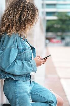 Jovem mulher latina usando seu telefone celular em pé ao ar livre na rua. conceito urbano.