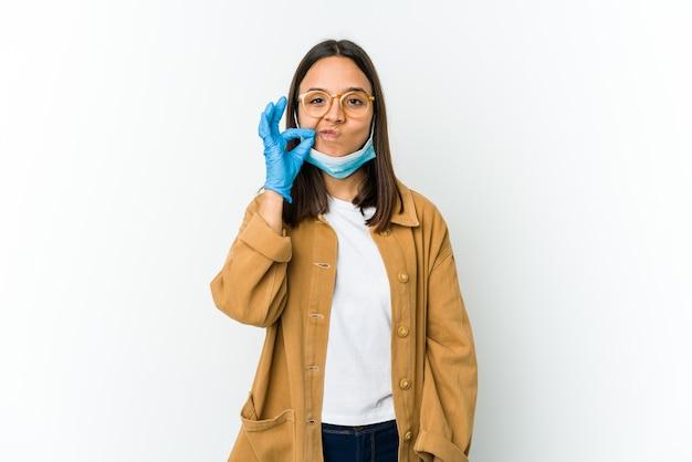 Jovem mulher latina usando uma máscara para se proteger de cobiçoso isolado no branco com os dedos nos lábios, mantendo um segredo.