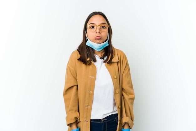 Jovem mulher latina usando uma máscara para se proteger de cobiçoso isolado no fundo branco encolhe os ombros e abre os olhos confusos.