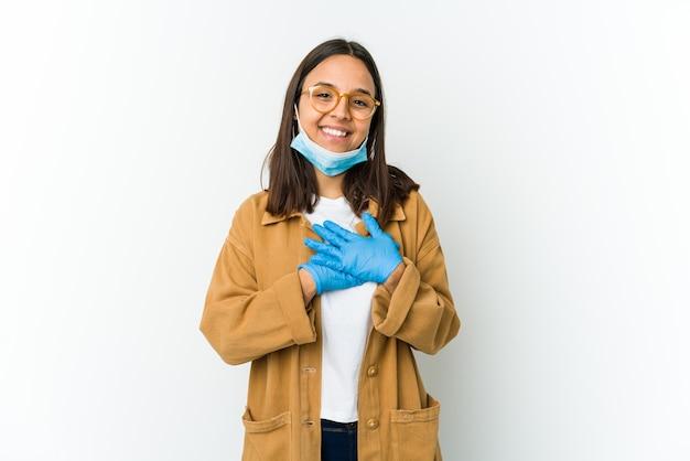 Jovem mulher latina usando uma máscara para se proteger de cobiçoso isolado no fundo branco tem uma expressão amigável, pressionando a palma da mão no peito. conceito de amor.