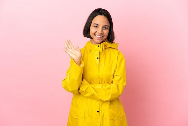 Jovem mulher latina vestindo um casaco à prova de chuva sobre um fundo isolado saudando com a mão com expressão feliz