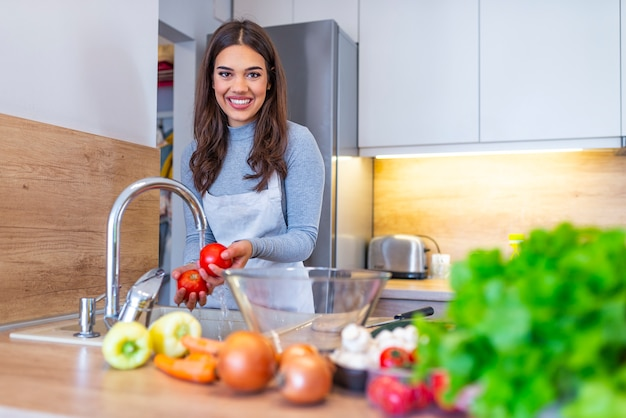 Jovem mulher lava os legumes na cozinha doméstica