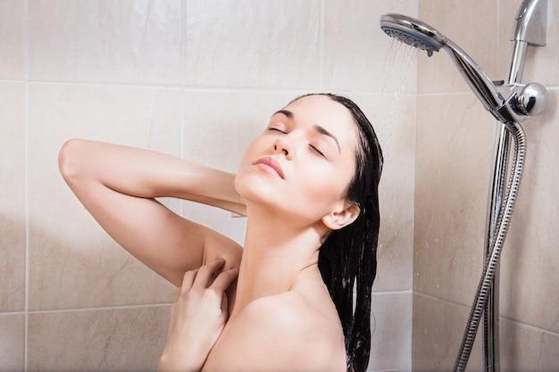 Jovem mulher lavando a cabeça debaixo do chuveiro