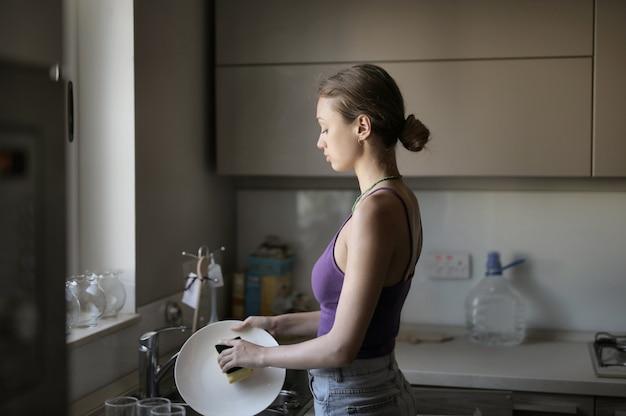 Jovem mulher lavando a louça na cozinha sob as luzes