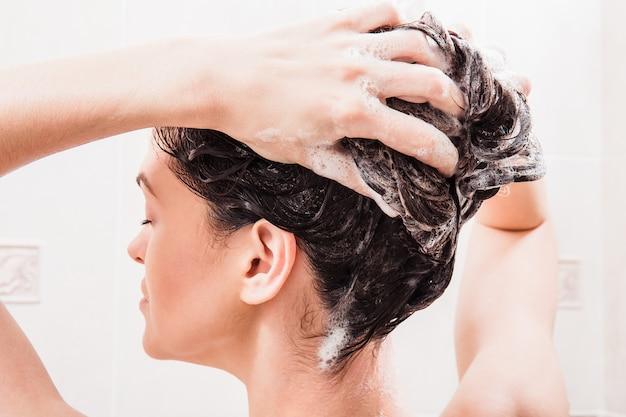 Jovem mulher lavando o cabelo com o shampoo no chuveiro